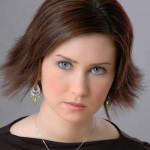 Attractive young woman with brown hair and stylish haircut; making direct eye contact with viewer