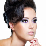 Beautiful face of a glamour woman with modern curly hairstyle and brightly makeup